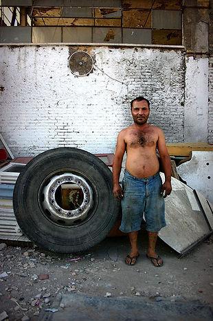uomo di etnia rom accanto ad un pneumatico, campo nomade - Roma, metropoliz, museo dell'altro e dell'altrove.