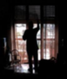figura in controluce che toglie la polvere, finestrone, testo creativo, maranola, casa