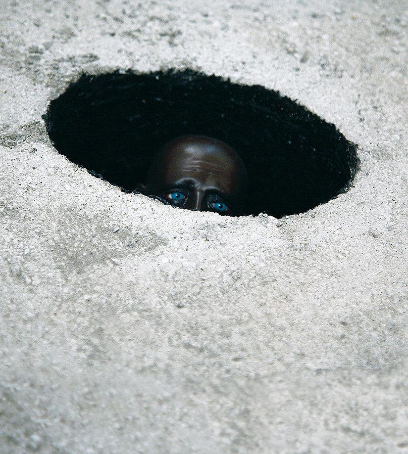 installazione di carlo de meo alla fondazione VOLUME!, figura scura in un buco con gli occhi azzurri, ombra e luce