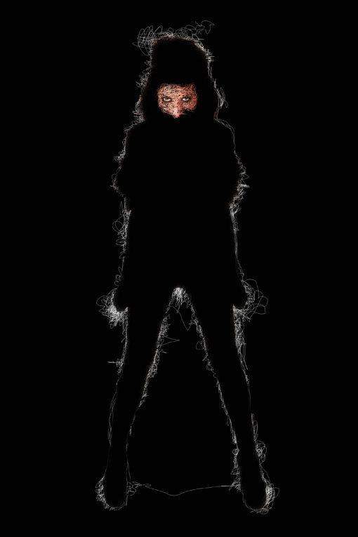 figura femminile in nero con aura bianca - sguardo penetrante e posizione di sfida