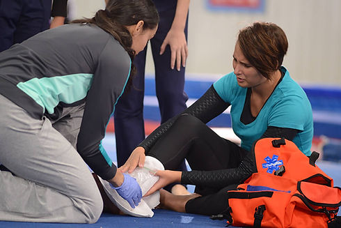 woman performing first aid for ankle inj