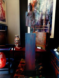 Buddha on wooden plinth