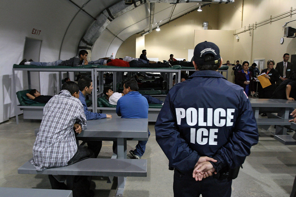 In this 2008 file photo, an Immigration and Customs Enforcement (ICE) officer guards a group of immigrants awaiting deportation at a Texas detention facility. (Jose Cabezas/AFP/Getty Images)