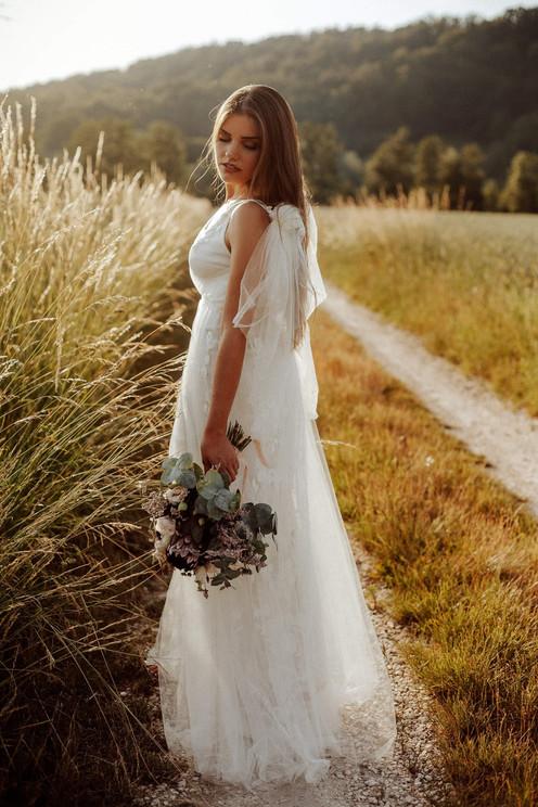 Braut auf Feld mit Brautstrauß