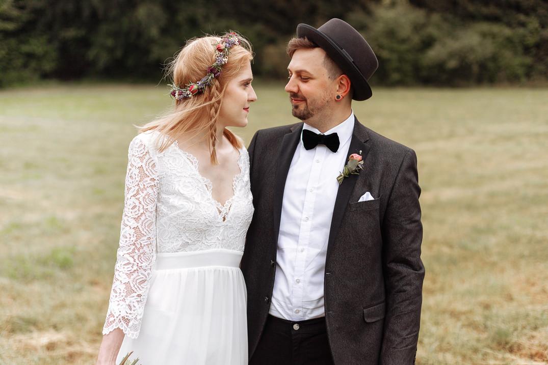 Brautpaar steht auf der Wiese