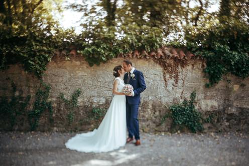 Brautpaar vor Mauer mit Grünzeug
