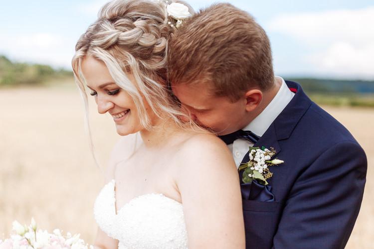 Bräutigam küsst Braut auf Schulter