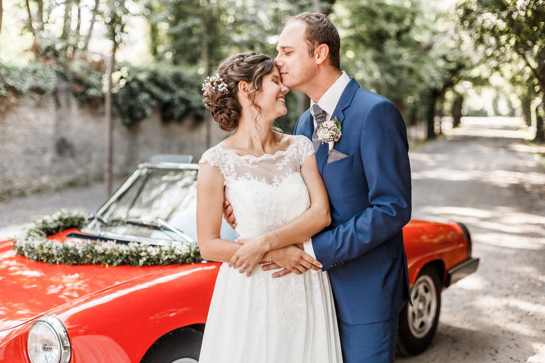 Brautpaar vor rotem Auto