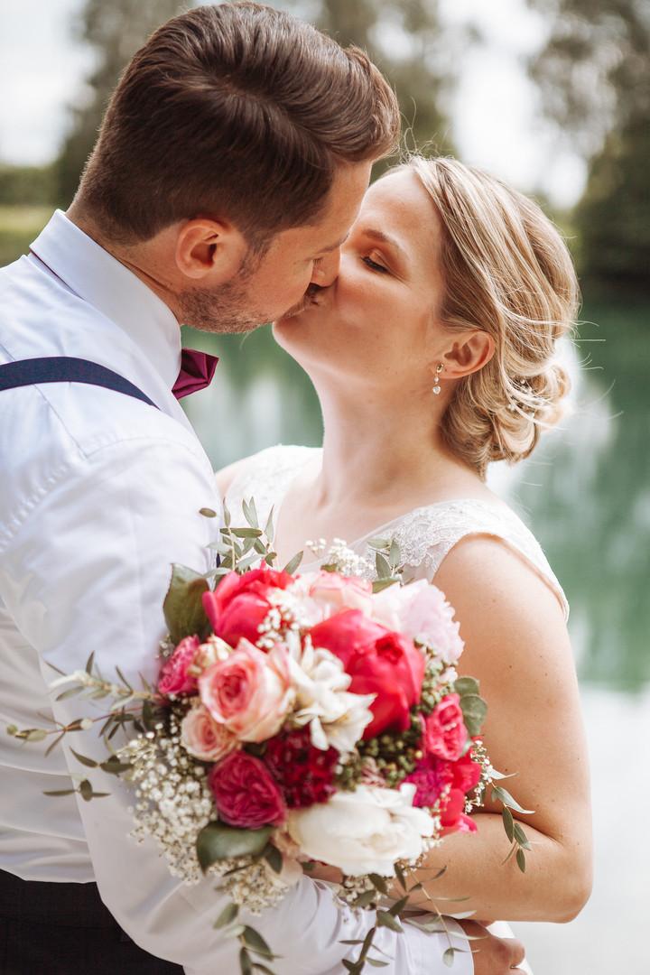 Brautpaar küsst sich am See