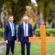 Tobias Göck und Richard Göck stehen vor eine Grab mit einem Grabkreuz, Holzkreuz