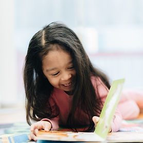 pre-k-diverse-girl-at-home-reading-from-a-book-GTEVB5W.jpg
