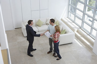 Man ad woman holding documents and shaking the hand of a gentleman in a suit. They are standing in a living room.