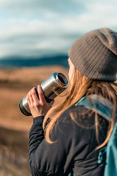 girl wearing a beanie taking a drnk from a stainless steel water bottle