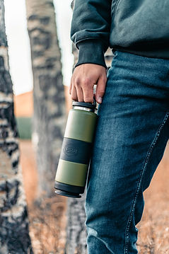 man wearing bluejeans holding a forest green stainless steel water bottle with black band
