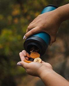 blue water bottle spilling dried fruit into hands