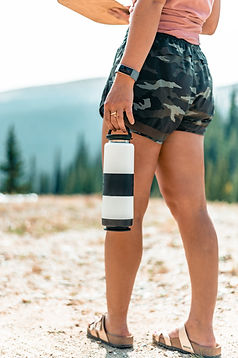 girl standing outside wearing camo shorts and sandles with a smart watch holding a white water bottle at her side