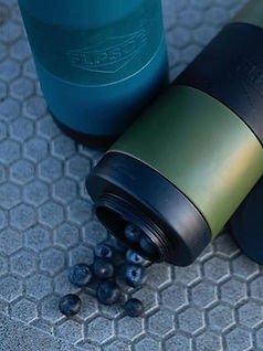 green water bottle with blueberries spilling out