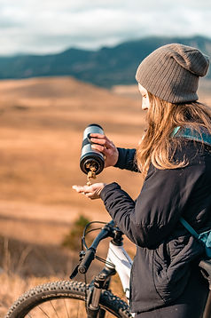 girl wearing winter clothes standing next to her mountain bike outside and pouring granola into her hand from a steel water bottle