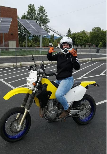 Aubrey Godbey is sitting on a motorcycle in a parking lot.  She is wearing a helmet, gloves, long sleeve shirt, jeans and boots.  She has both her hands up giving the Hang Loose sign.  The Motorcycle is a dual-purpose mortorcycle.
