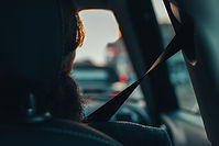 Image of a vehicle occupant wearing a seatbelt.  Image is from the back seat of the vehicle.