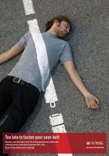 """A lifeless man is laying on his back on the road surface.  The white dashed lines from the roadway from a seatbelt over his chest.  The seat belt crosses his chest and touches the ground near his waist.  The white line then forms an image of an unbuckled seatbelt.  It states, """"Too Late to fasten your seat-belt.""""  Photograph by Yianni Hill and Reed Young for the United Nations WoHO Road Safety Campaign in 2007"""