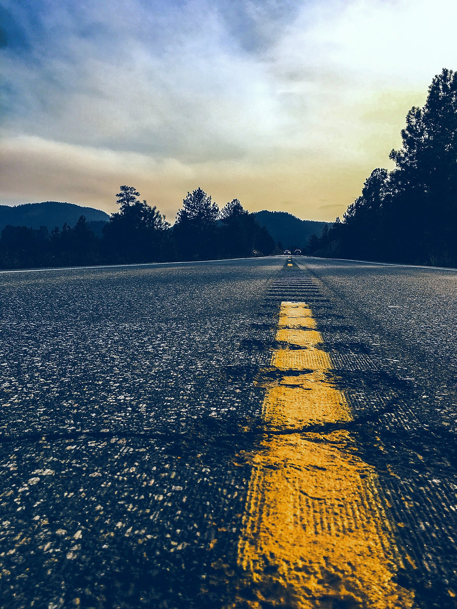 Close up image of yellow stripe on roadway with trees off in the distance
