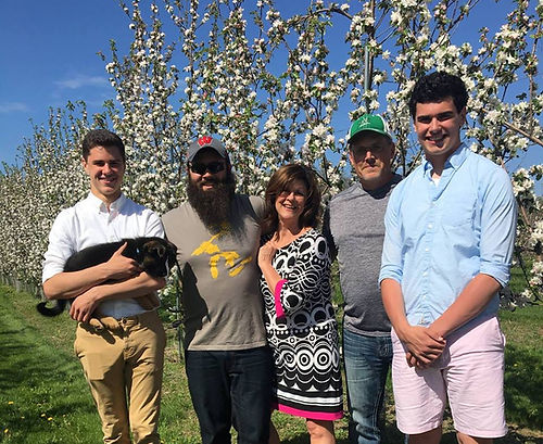 A family with two parents, three sons, and a puppy standing in front of apple trees in bloom