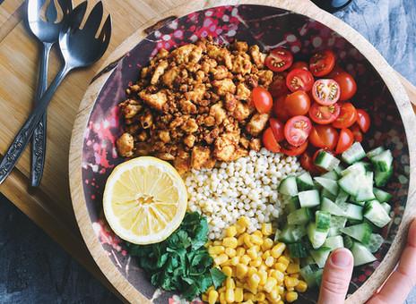 Salade de couscous israélien aux pépites de tofu cajun, maïs, tomates, concombre et coriandre.