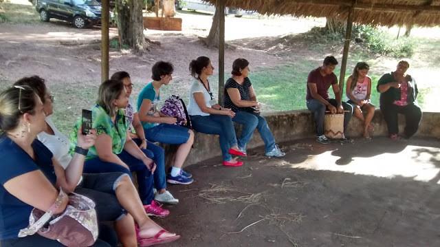 A foto mostra um grupo de pessoas sentadas em uma roda de conversa.