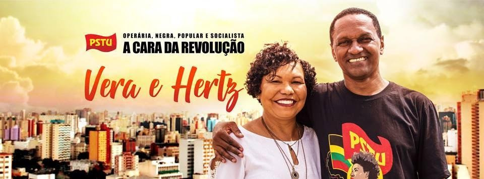 A foto mostra uma mulher e um homem com a o braço nos ombros dela. Os dois são negros e os dois sorriem. Ela usa uma blusa branca e um colar. Ele veste a camiseta do PSTU. A mensagem ao lado diz: Operária, negra, popular e socialista - A cara da revolução. Vera e Hertz.