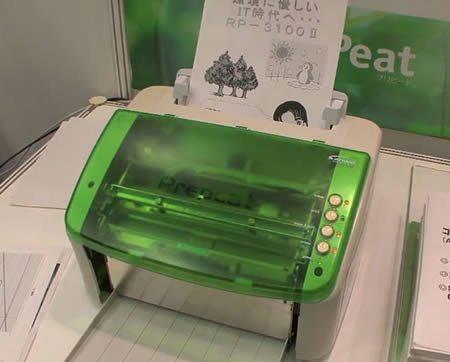 A foto mostra uma impressora verde. Ao redor tem várias folhas de papel.