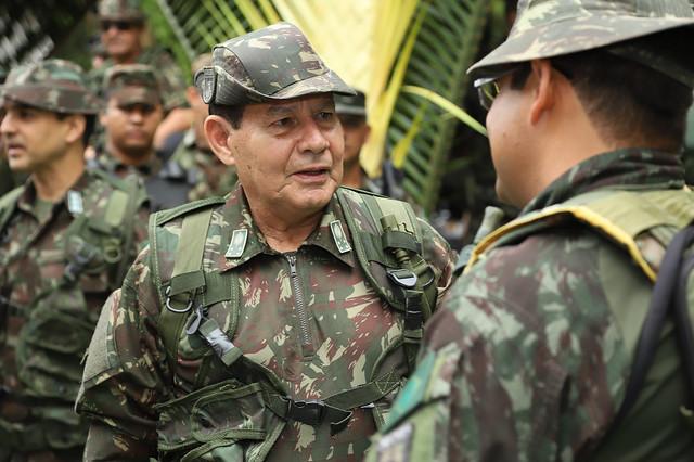 A imagem mostra a foto de militares. Ao fundo, algumas pessoas desfocadas. No centro, está o Vice-Presidente Hamilton Mourão. Ele usa a farda militar (macacão verde com estampa de camuflagem e o chapéu com a mesma estampa).
