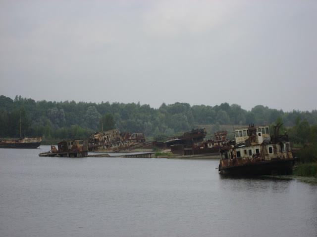 A foto mostra um lago com barcos abandonados.