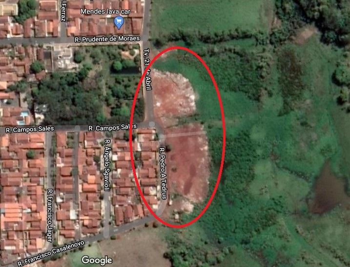 A imagem mostra a área que corresponde ao aterro vista por satélite. A imagem mostra o terreno verde e ao lado as casas em tom marrom. Possui uma pequena área verde entre as casas.