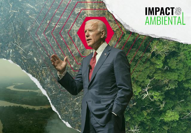 A imagem mostra Joe Biden que usa um terno azul e gravata vermelha. Ele tem cabelo branco e é caucasiano. Ele está com mão direita levantada e a mão esquerda dentro do bolso. Ao fundo. se vê a Floresta Amazônica com uma parte desmatada. Essa parte destruída está chegando na floresta ainda em pé. Também dá para ver o rio Amazonas no canto esquerdo inferior. No canto direito superior, está o logo do Impacto Ambiental.