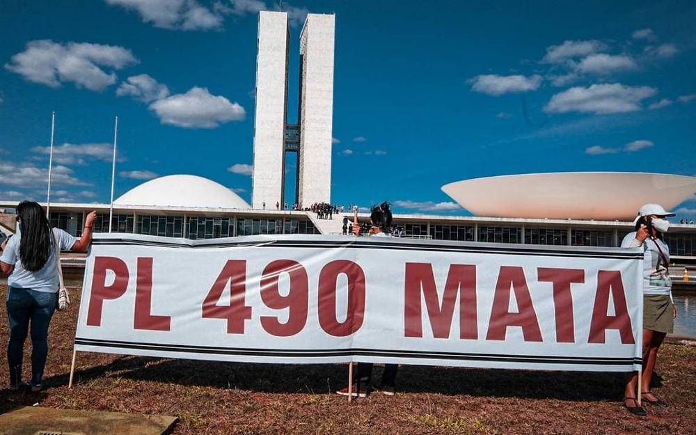 """Indígenas protestam em frente ao Congresso Nacional e seguram cartaz com os dizeres """"PL 490 mata""""."""