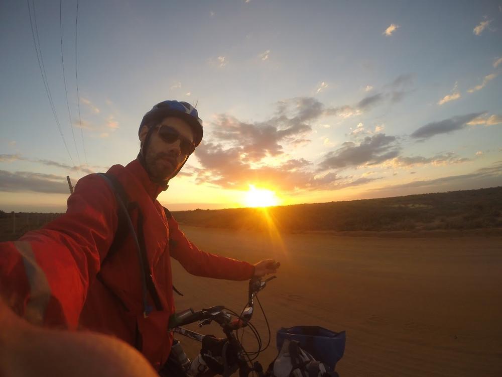 A foto mostra um homem, branco, contra o sol, ele usa capacete de bicicleta, usa jaqueta vermelha e óculos escuros. Ele está tirando uma selfie em cima de uma bicicleta.