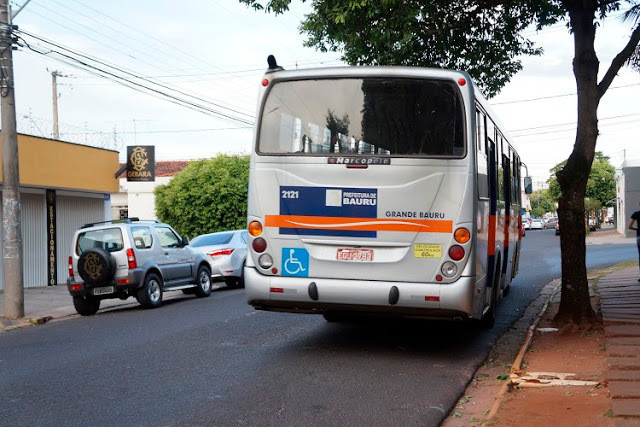A foto mostra um ônibus passando pela rua. Há dois carros estacionados.