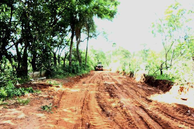 A foto mostra uma estrada de terra e um trator passando por ela.