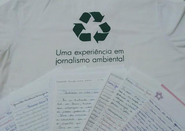"""A foto mostra a camiseta escrito: """"Uma experiência em jornalismo ambiental"""", e embaixo está as folhas de redação uma do lado da outra."""