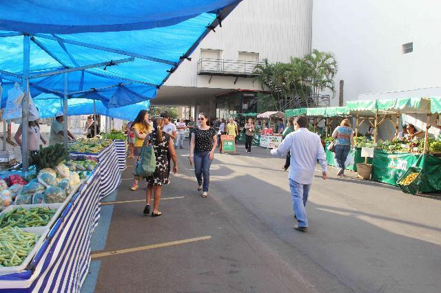 Pessoas andando nas feiras. Nos dois lados da rua tem barracas com alimentos expostos.