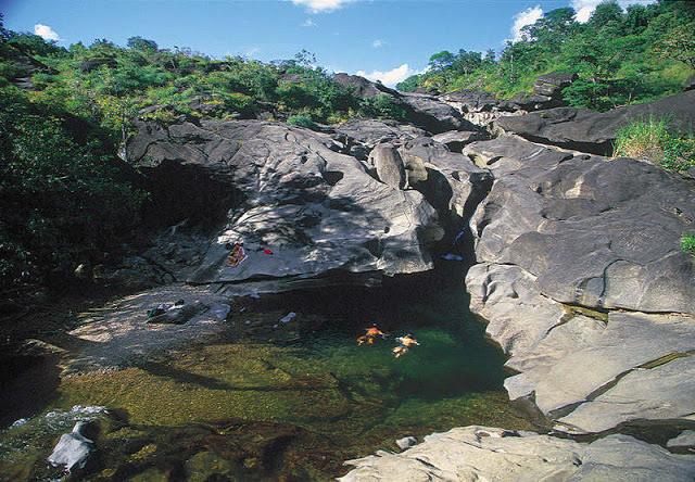 Pessoas nadando no lago em região montanhosa