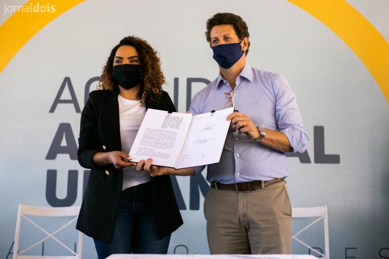 A imagem mostra a prefeita de Bauru, Suéllen Rosim, junto do Ministro do Meio Ambiente, Ricardo Salles, segurando juntos um documento. Os dois usam máscaras.