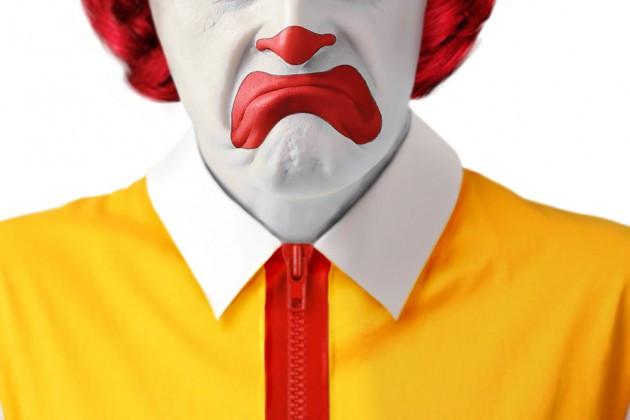 A foto mostra o palhaço do McDonald's com uma cara triste, a foto só mostra o nariz para baixo. É um homem com a cara pintada de branco, ponta do nariz vermelho, batom borrado de vermelho, ele usa uma jaqueta amarela com zíper vermelho e lapela branca.