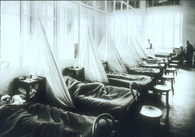 A foto mostra homens doentes com a gripe em camas de hospital. A foto está em preto e branco. O hospital é antigo e ficava num acampamento militar.