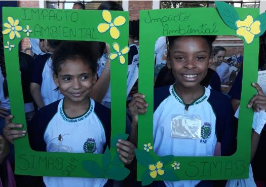 Duas crianças tiram fotos com a moldura Impacto Ambiental/SIMAB 2019. Elas são meninas, negras, mais ou menos 10 anos e estão sorrindo.