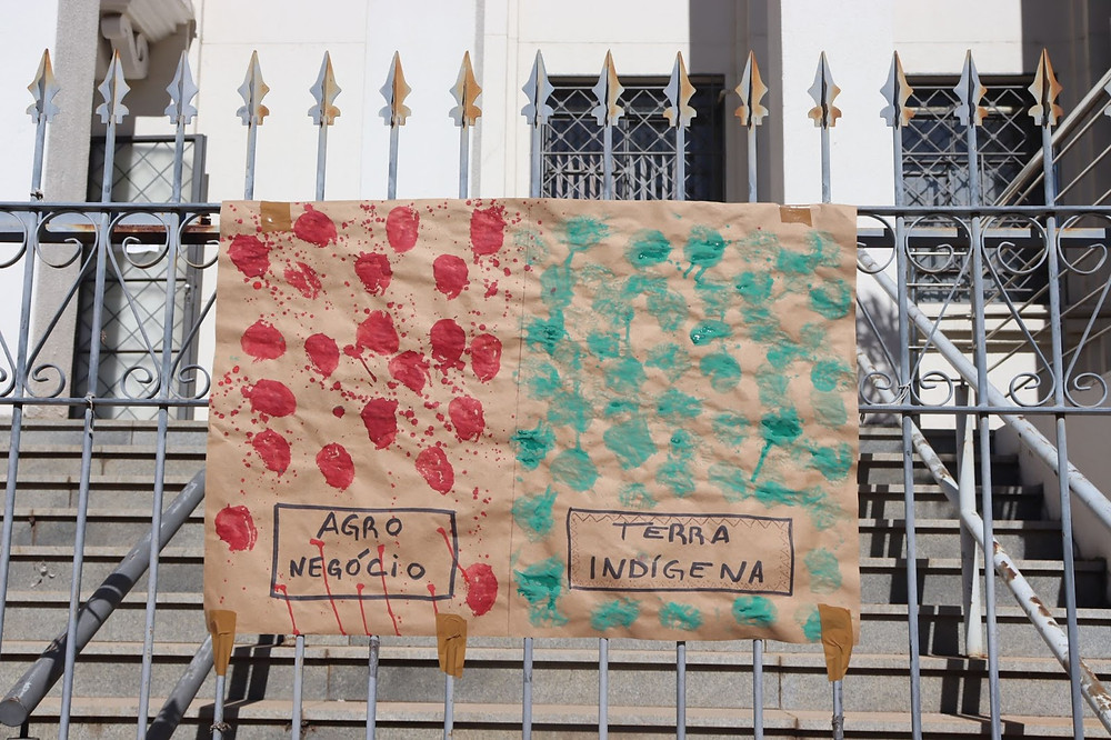 """Cartaz com os dizeres no lado esquerdo """"agronegócio"""" e pintado em tinta vermelha, enquanto no lado direito está escrito """"terra indígena"""" e pintado com tinta verde."""