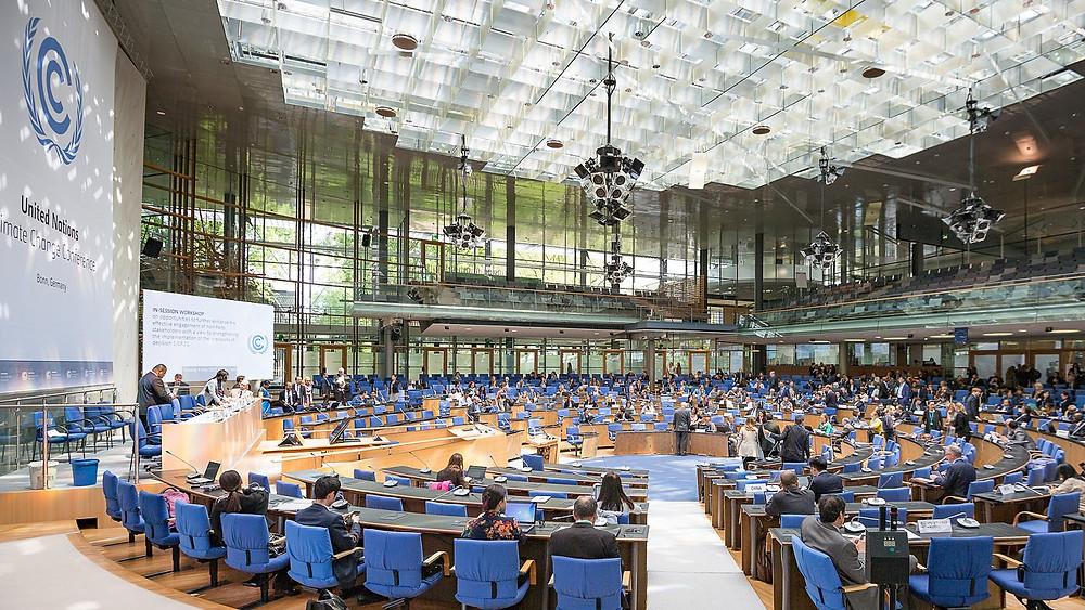 A foto mostra uma grande sala de conferência, com cadeiras azuis enfileiradas na horizontal, tem um palanque no meio.