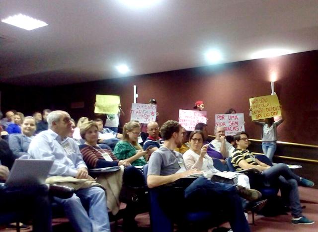 A foto mostra várias pessoas sentadas uma do lado da outra em um auditório. Ao fundo manifestantes levantam cartazes.