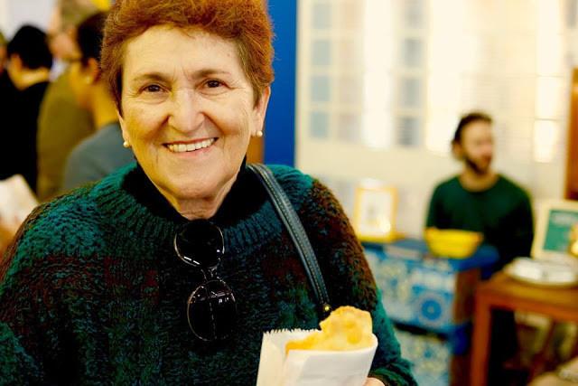 Mulher sorrindo mostra seu pastel.